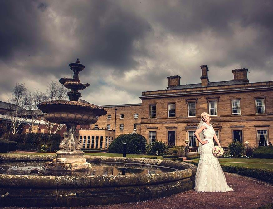 bride next to fountain with oulton hall in background